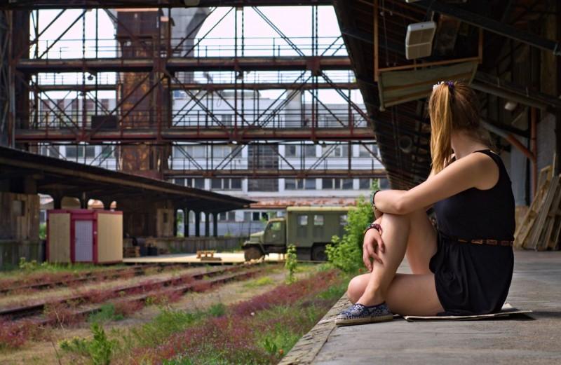 Nákladové nádraží Žižkov, abandoned freight train station, Tina sitting on the ground